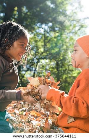 Kids holding leaves - stock photo
