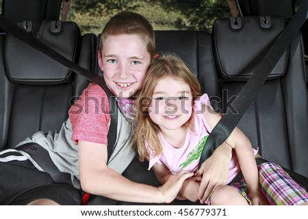 Kids hugging in the back of a car