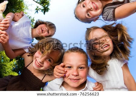 Kids in a huddle having fun and looking down - stock photo