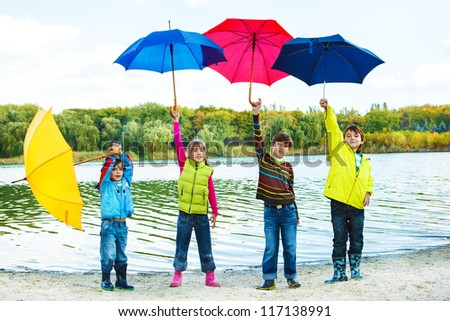 Kids in autumn clothing holding colorful umbrellas - stock photo