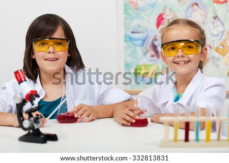 Kids in elementary science class doing chemical experiments-focus on boy face - stock photo