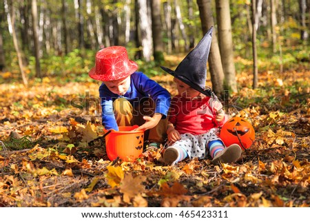 kids in halloween costume play at autumn park, trick or treating