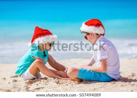 Kids in red Santa hats having fun at tropical beach during Christmas vacation