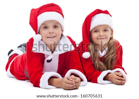 Kids in santa costumes at christmas time laying on the floor - isolated - stock photo