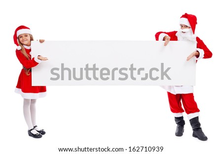 Kids in santa costumes offering you a copy space on white banner - isolated - stock photo