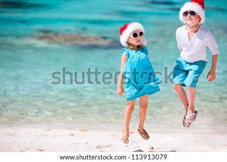 Kids in Santa hats having fun at tropical beach - stock photo