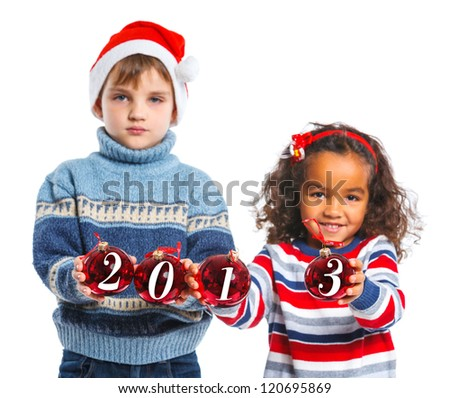 Kids in Santa's hat holding a christmas ball with 2013 against a white background. Focus on the ball - stock photo