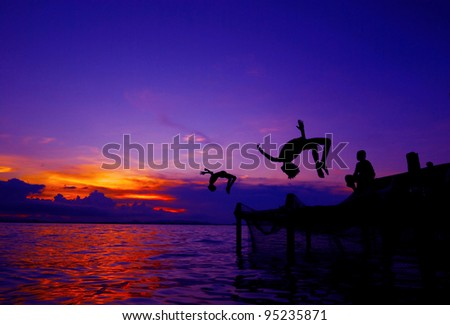 Kids in silhouette doing back-flip jump to the water - stock photo