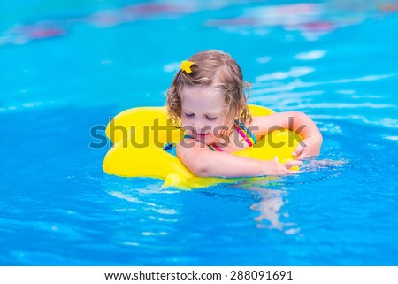 Kids in swimming pool. Children swim outdoors. Toddler child during vacation in a tropical resort with palm trees. Little girl playing on a beach. Active kid in summer with colorful toy floating ring.