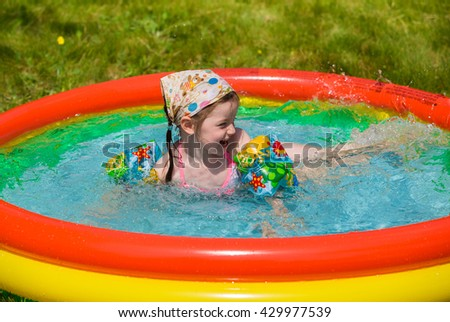 Kids in swimming pool. Children swim outdoors. Toddler child during vacation. Little girl playing on a beach. Active kid in summer with colorful toy floating ring. - stock photo