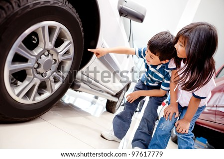 Kids in the dealer looking at car wheels - stock photo