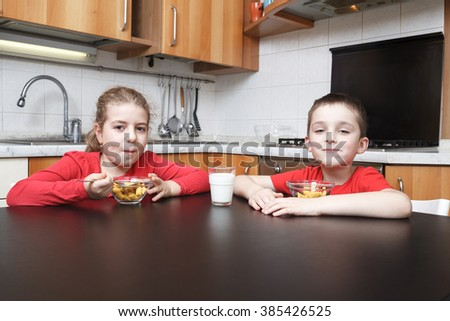 kids in the kitchen eating cereals - stock photo