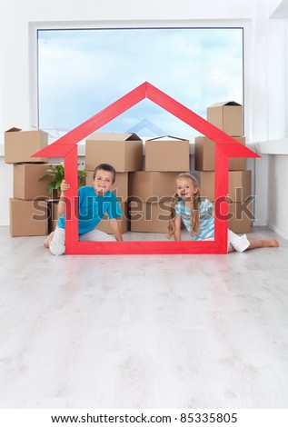 Kids in their new home holding large house shaped frame - moving concept with copy space - stock photo