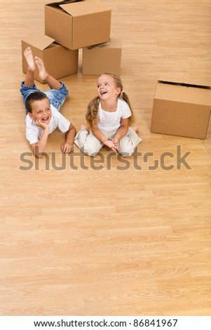 Kids in their new home with cardboard boxes - large copy space - stock photo