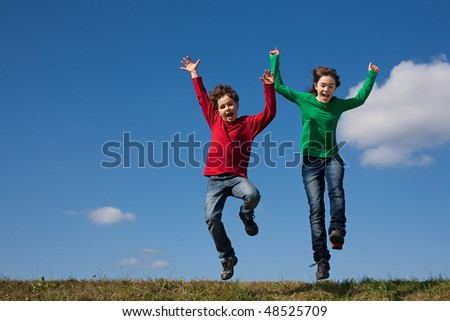 Kids jumping against blue sky - stock photo