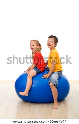 Kids jumping and having fun on a large rubber exercise ball - isolated - stock photo