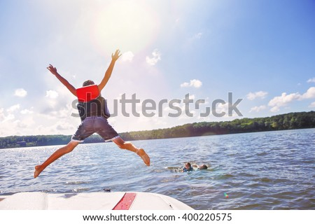 Kids jumping off a boat into the lake. Focus on boys legs and boat, lens flares from sun. - stock photo