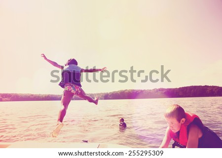 Kids jumping off a boat into the lake. Instagram effect. - stock photo