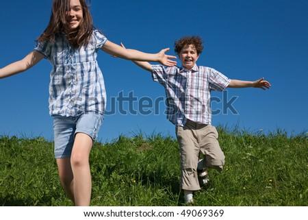Kids jumping, running against blue sky - stock photo