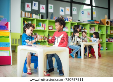 kids kindergartner in group of preschool are playing and in attention of learning drawing subject in classroom and enjoy learning together