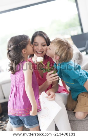 kids kissing their mother and offering a flower - stock photo