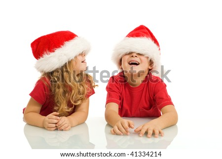 Kids laughing and having fun with christmas hats - isolated - stock photo