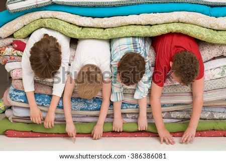 Kids laying inside the pile of mattresses and having fun. slumber party. funny activities with children indoors. - stock photo