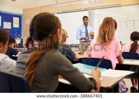 Kids listening to teacher at an elementary school class - stock photo