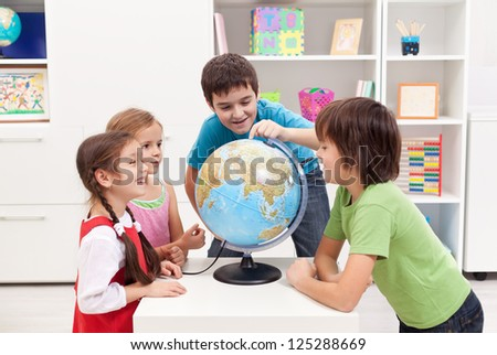 Kids looking at earth globe and telling stories - stock photo