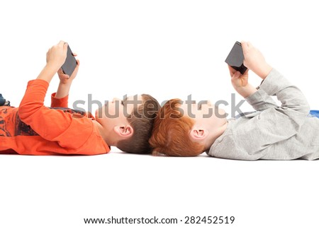 Kids lying down playing on mobile phones