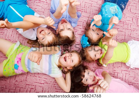 Kids lying on the floor and looking into camera - stock photo