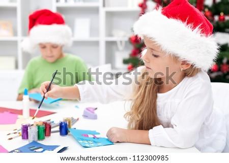 Kids making christmas greetings wearing santa hats - stock photo