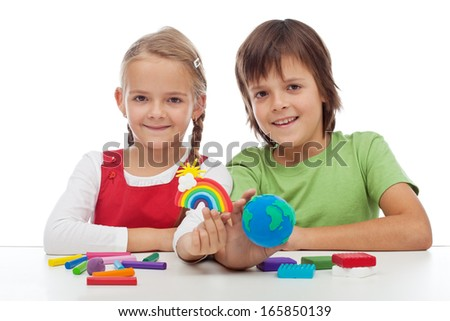 Kids making colorful ecology theme clay figures - holding earth globe and rainbow - stock photo