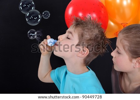 kids making soap bubbles - stock photo