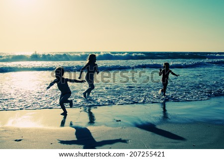 kids on the beach at sunset - stock photo