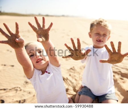 Kids on the beach show their sand covered hands to the camera - stock photo