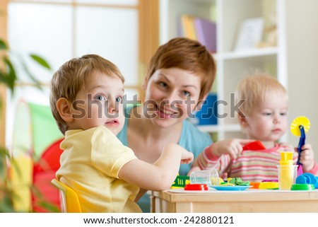 kids or children and mother play colorful clay toy at home - stock photo