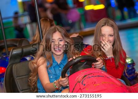 kids or teens on fairground ride dodgem bumper cars    - stock photo