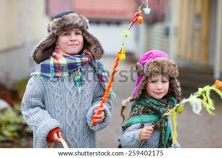 Kids outdoors dressed for Easter traditional celebration in Finland - stock photo