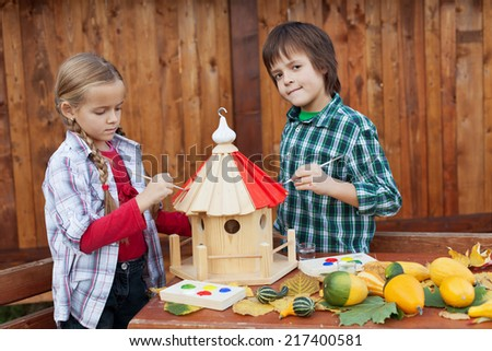 Kids painting a bird house in autumn - stock photo