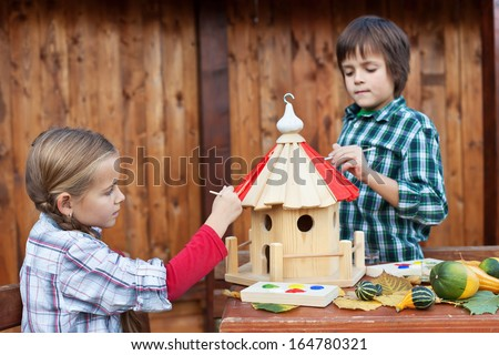 Kids painting the bird house for the winter - care for nature concept - stock photo