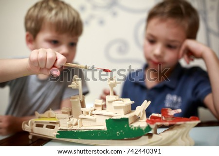 Kids painting wooden model of warship at home