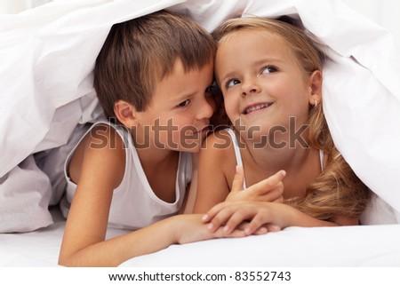 Kids planning the next prank hidden under the quilt - stock photo