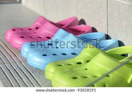 Kids plastic summer clogs in a row on a step. Shot through glass. Shallow depth of field. Focus on the Blue clog. - stock photo