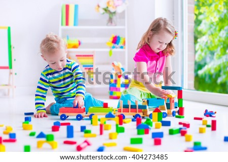 Kids play at day care. Two toddler children build tower of colorful wooden blocks. Child playing with toy train. Educational toys for preschool and kindergarten. - stock photo