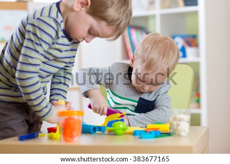 Kids Play Modeling Plasticine, Children Mold Colorful Clay Dough.  Preschooler Playing Together - stock photo