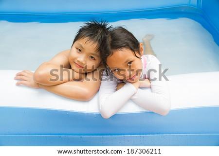 Kids play swim in inflatable plastic pool. - stock photo
