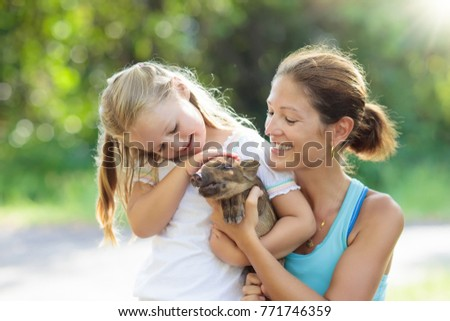 Kids play with farm animals. Child feeding domestic animal. Young mother and little girl holding wild boar baby at petting zoo. Kid playing with newborn pig. Children and pets Family at farm vacation.