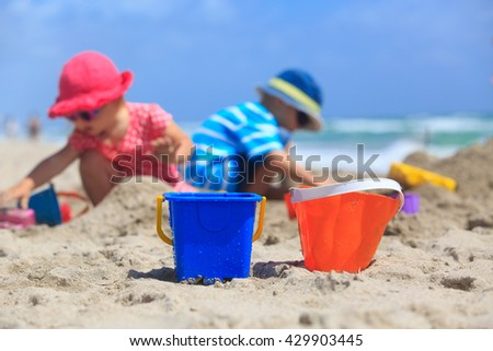 kids play with sand on beach