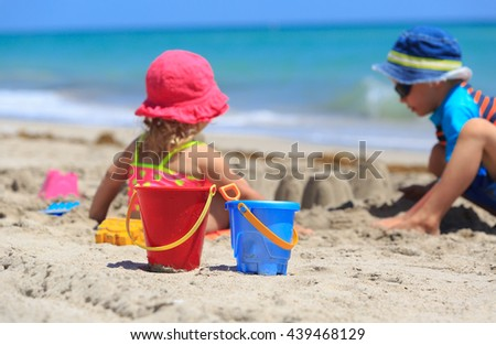 kids play with sand on beach - stock photo